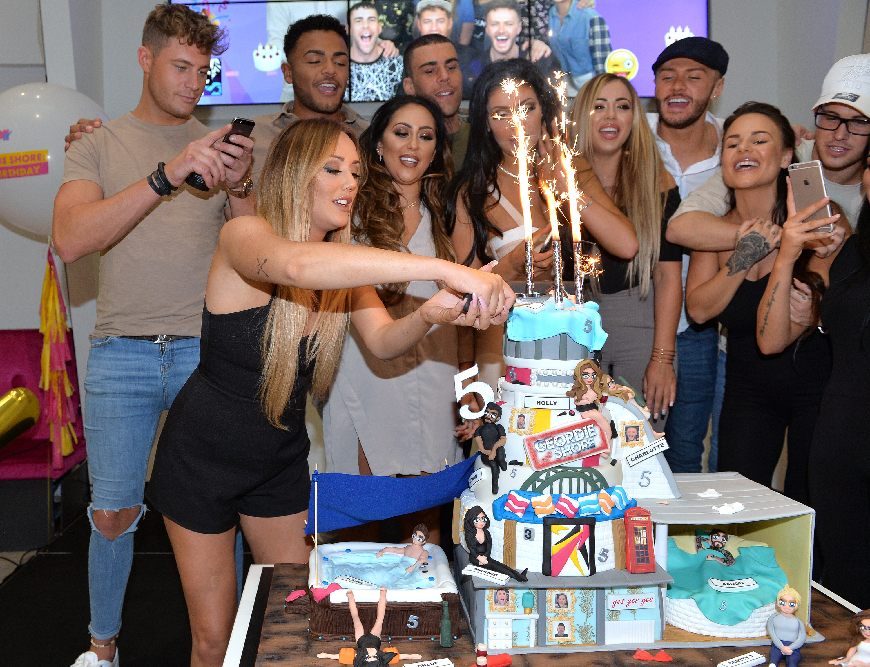 LONDON, ENGLAND - MAY 24: Charlotte-Letitia Crosby cuts the birthday cake with Holly Hagan, Chloe Etherington, Chantelle Connelly, Marnie Simpson, Sophie Kasaei, Aaron Chalmers, Nathan Henry, Scott Timlin, Marty McKenna, James Tindale and Dan Thomas-Tuck of Geordie Shore celebrate their fifth birthday at MTV London on May 24, 2016 in London, England. (Photo by Anthony Harvey/Getty Images) *** Local Caption *** Charlotte-Letitia Crosby; Holly Hagan; Chloe Etherington; Chantelle Connelly; Marnie Simpson; Sophie Kasaei; Aaron Chalmers; Nathan Henry; Scott Timlin; Marty McKenna; James Tindale; Dan Thomas-Tuck